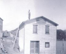 Historic image of Mr. Bill Wakeham tarring the roof of the sawmill while it was in its first location in Petite Forte.  Photo pre 1940.; HFNL/ 2006