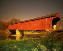 The West Montrose Covered Bridge, viewed from the south bank of the Grand River.; Ontario Tourism Marketing Partnership