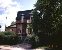 Charming mid-1870s home features original porch with panelled doors, decorated dormer windows above; City of Ottawa 2005