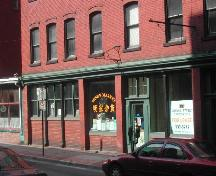 Photograph displaying the storefront and detailing the cast iron pillars, storefront cornice, entrance, and window designs; City of Saint John 2004