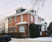 This image illustrates the two-storey east and north brick-clad facades of the George Durrand Residence with prominent Edwardian-era features such as symmetrical composition and classically influenced front veranda.; City of Edmonton, 2004
