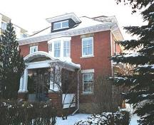 This image illustrates the two-storey north and west brick-clad facades of the George Durrand Residence with prominent Edwardian-era features such as symmetrical composition and the classically influenced front veranda.; City of Edmonton, 2004