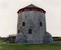 Exterior view of the Martello tower located at Point Frederick Buildings National Historic Site of Canada, 1993.; Department of National Defence / Ministère de la Défense nationale, 1993.