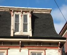 This photograph shows the mansard roof and the sharp flare that it possesses. The photo also shows a dormer window and artistic brackets, 2006; City of Saint John