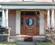 This image provides a view of the entrance flanked by Corinthian pilasters and consisting of a stained glass transom window, sidelights and a wooden door with a rounded, glass panel, 2006 ; City of Saint John