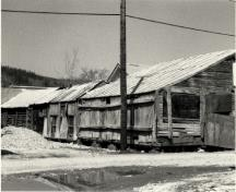 Rear view of Lowe's Mortuary, showing the log and wood frame construction, 1987.; Agence Parcs Canada / Parks Canada Agency, 1987.