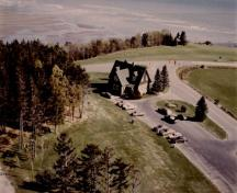Bird's eye view of the Administration Building, showing the building's picturesque design and location in an open setting which in turn emphasizes the rustic nature of the setting, c. 1980.; Parks Canada Agency / Agence Parcs Canada, c./vers 1980.