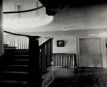 Interior view of the Former Superintendent's Residence, showing the surviving interior details, such as the woodwork and the curved staircase, 1989.; Parks Canada Agency / Agence Parcs Canada, 1989.