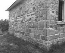 Corner view of the Jones Falls Defensible Lockmaster's House, showing the exterior walls, constructed of rough-faced masonry blocks, 1989.; Parks Canada Agency / Agence Parcs Canada, 1989.