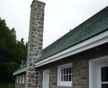 View of the exterior of the Bathhouse, showing the exterior materials and finishes, particularly the rough-cut, irregularly coursed stone, wood trim, and cedar roof shingles.; Parks Canada Agency / Agence Parcs Canada.