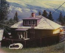 Rear view of the Upper Hot Pool Residence, showing its one-and-a-half storey structure of standard platform frame construction, with a rectangular plan and medium-pitch gable roof, 1990.; Parks Canada Agency / Agence Parks Canada, 1990.