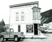 View of the main entrance to Harrington's Store (15), showing the square-sided oriel window placed at the salient angle, the richly ornamented double front door, and the painted cove siding, 1987.; Department of the Environment / Ministère de l'Environnement, 1987.