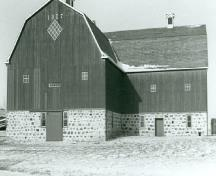 General view of the Barn, showing the L-shaped gambrel-roofed structure built of stone and timber, 1988.; Agence Parcs Canada, Homestead Motherwell/ Parks Canada Agency, Motherwell Homestead, 1988.