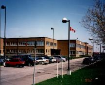 Corner view of the National Film Board complex, showing Block A and the parking lot, 1998.; Public Works and Government Services Canada / Travaux publics et Services gouvernementaux Canada, 1998.