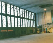 Interior view of the Air Terminal Building (H-7), showing the concrete foundation and floor and the wood framing with steel bracing around the hangar doors.; Transport Canada / Transports Canada