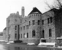 Façade of the Armoury, showing the prominent three-storey projecting frontispiece, consisting of a troop door and two flanking stair towers, 1989.; Parks Canada Agency / Agence Parcs Canada, J. Adell, 1989.