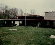 General view of the Cottage, showing the single storey, horizontal massing and the tripartite composition, 1989.; Environment Canada / Environnement Canada, 1989.