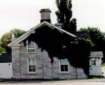 Corner view of RMC Building 2, showing the picturesque qualities of its design and form which complement a domestic garden, picket fence and mature trees, 1993.; Parks Canada Agency / Agence Parcs Canada, 1993.