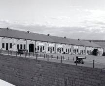 General view of the Commissariat Stores / Reverse Fire Chamber East, showing the long moderately pitched hipped roof pierced at intervals by squat masonry chimney stacks, 1996.; Parks Canada Agency / Agence Parcs Canada, 1996.