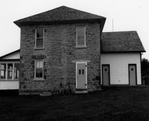 Side view of the Defensible Lockmaster's House, showing the exterior walls constructed of stone masonry and the rear kitchen addition, 1989.; Department of Public Works / Ministère de l'Approvisionnement et des Services, 1989.