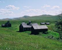 View of Bar U Ranch, showing the simple massing, modest proportions and medium-pitched roofs of the buildings, 1993.; Parks Canada Agency / Agence Parcs Canada, J.P. Jérôme, 1993.