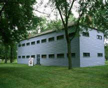 General view of Butler's Barracks showing the Soldiers' Barracks in its rectangular, two-storey massing under low, hipped roof, brick wall infill, and regularly placed, horizontally shaped windows, 1994.; Parks Canada Agency / Agence Parcs Canada, B. Morin, 1994.