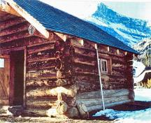 Corner view of the Halfway Hut showing the use of natural, local materials consistent with the principles of rustic architecture such as the horizontally laid peeled log construction, boulder foundation, and wood shingle roof.