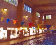 General view of the interior of the Swimming Pool RR22A showing the successful integration of traditional wood elements such as the glue laminated timbers with modern masonry elements such as the concrete surfaces and tile wainscoting, 2000.; Department of National Defence / Ministère de la Défense nationale, 2000.