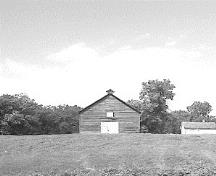 View of the exterior of Fort Dufferin stable, showing its relatively isolated setting within a meadow.; Parks Canada Agency / Agence Parcs Canada.