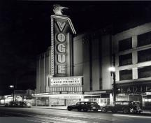 General view of Vogue Theatre, showing the tall sign tower that dominates the facade, outlined in neon and surmounted by a stylized figure of the goddess Diana.; Vancouver Public Library, Historical Photo Collection, 33461.