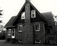 Side view of the Superintendent's Residence, showing the steeply pitched, shingled, gable roof with a stone chimney, c. 1990.; Parks Canada Agency / Agence Parcs Canada, c./v. 1990.